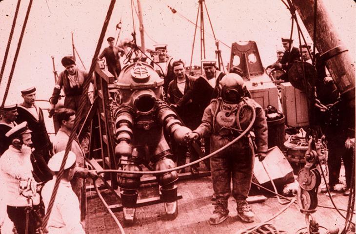 استكشاف جي. بيريز مرتديًا لباس غوص طراز ١- جو [وحدة عالمية لقياس الضغط] من شركة تريتونيا، لحطام سفينة لوسيتانيا في ١٩٣٥. جيم جاريت كان هو الغواص الرئيسي وغاص لمسافة ٣١٢ قدم.