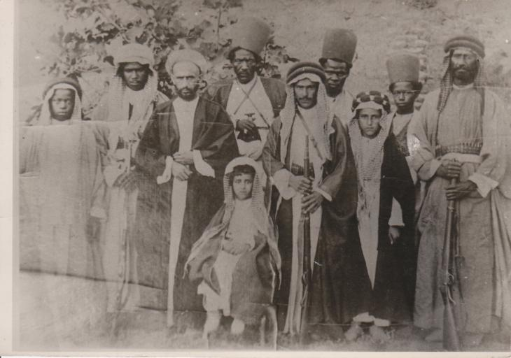 A young Shaikh Abdullah seated (centre) and a number of retainers, 1908. Public Domain